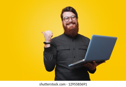 Cheerful bearded man is holding laptop and poiting bkack, looking at camera over yellow background