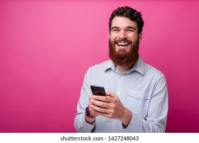 Cheerful bearded man looking at the camera and typing something on his phone.