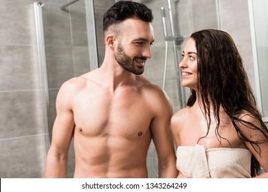 cheerful bearded man looking at smiling brunette woman in bathroom