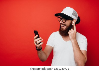 Cheerful bearded man using airpods and looking at phone over red wall