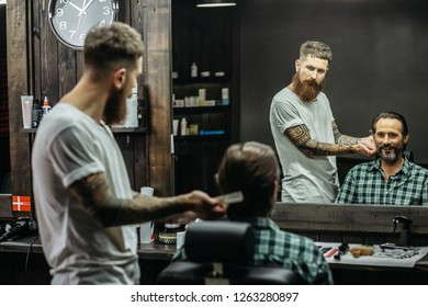 Cheerful bearded middle aged man smiling and looking at his reflection in the mirror while professional tattooed barber working