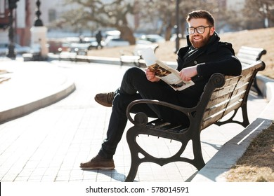 Cheerful bearded young man in glasses sitting and reading newspaper on the bench outdoors