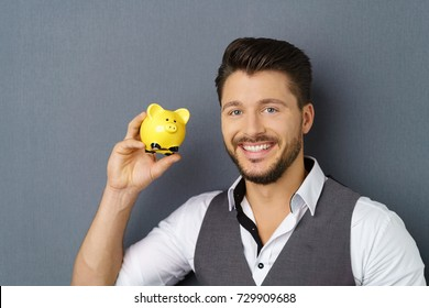 Cheerful bearded young man holding yellow piggy bank against dark background