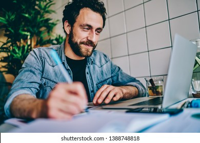 Cheerful bearded young man watching webinar online on website and writing down text notes for studying project sitting at computer in coworking.Hipster student watching tutorial and making notes