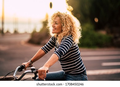 Cheerful beauiful blonde curly caucasian woman smile and enjoy the ride on a bike in outdoor leisure activity in the city - free and joyful active people on the street having fun