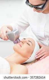 Cheerful beautician is undergoing laser treatment for female face. She is standing and wearing goggles. The woman is lying and relaxing. She closed her eyes with enjoyment