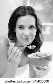 Cheerful beautiful brunette woman eating muslin, indoors. Healthy eating, beauty and dieting concept. Black and white.