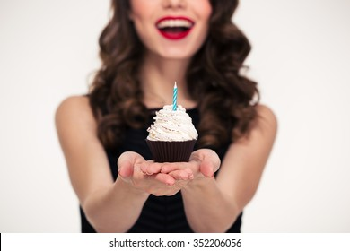 Cheerful beautiful curly young woman in retro style giving birthday cupcake with candle