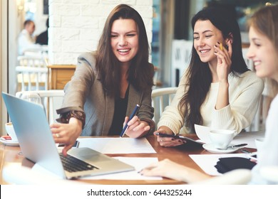 Cheerful beautiful female students with good mood laughing while watching funny useful webinar on modern laptop computer device sitting in coworking interior and using free 4G internet connection