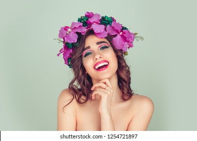 Cheerful beautiful girl flirting at camera. Young woman laughing with headband from orchid flowers floral crown hand touching face looking at you laughing Flirt and positive emotion expression on face