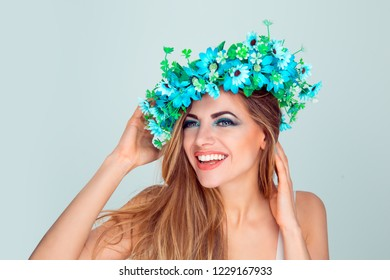 Cheerful beautiful girl flirting playing with her floral crown. Young woman with headband from blue flowers touching chin and hair posing looking ahead. Flirt and positive emotion expression on face