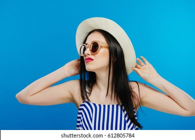 Cheerful beautiful girl in hat and sun glasses. Smiling widely, looking and pointing aside. Summer outfit. Waist up, studio, indoors