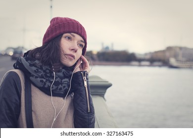 The cheerful beautiful girl in a leather jacket listening to music through white headphones on the Troitsky Bridge in Saint Petersburg