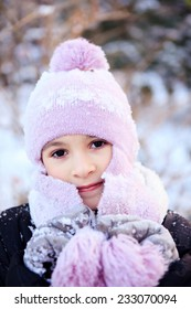Cheerful beautiful girl in purple winter hat in the snow under the Christmas tree