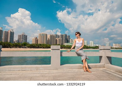 Cheerful and beautiful girl resting fun in vacation, on the pier on background of city. In China, Hainan city of Sanya. View of island in bay. Town Sanya is popular tourist destination in China