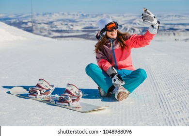 cheerful beautiful girl with snowboard sitting and taking selfies in the mountains
