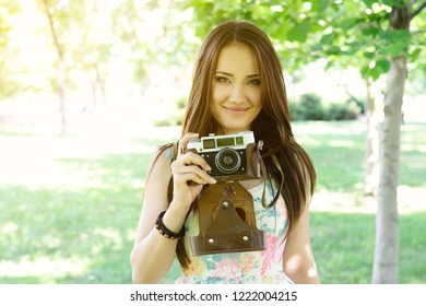 Cheerful beautiful girl talking pictures with vintage camera in summer park. Young woman photographer posing with her camera outdoor.