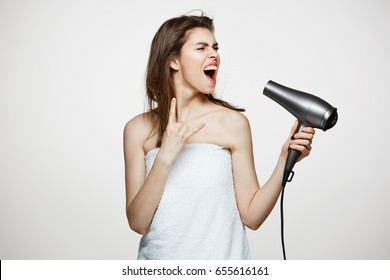 Cheerful beautiful girl in towel smiling laughing singing with hair dryer making funny face over white background. Beauty spa and cosmetology.