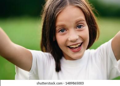 cheerful beautiful girl in a white t-shirt joy childhood fun nature