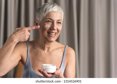 Cheerful beautiful mature woman holding jar of cosmetic product and applying cream on her face in cosy home, Beauty and cosmetic routine concept