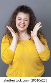 cheerful beautiful overweight girl laughing with euphoric smile and playful hands wearing yellow sweater