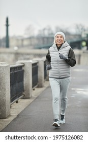 Cheerful beautiful senior woman in hat and gloves using smart watch while brisk walking along riverside in winter