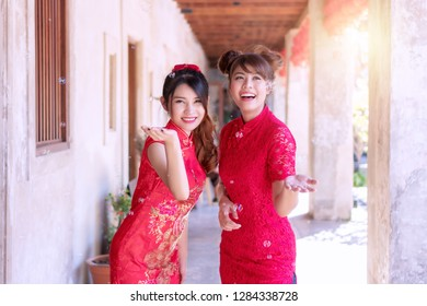 Cheerful beautiful smile two young woman friend wear cheongsam red dress holding hands looking at the soap bubble feeling fun. Festivities and Celebration concept