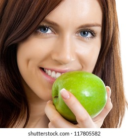 Cheerful beautiful woman eating apple, isolated over white background