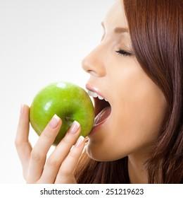 Cheerful beautiful woman eating apple
