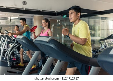 Cheerful beautiful woman with a healthy lifestyle drinking water during cardio training on treadmill in a trendy fitness club