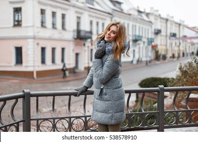 Cheerful beautiful woman in stylish winter clothes walking on a winter day in the city.