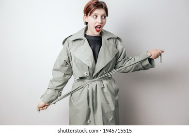 A cheerful, beautiful woman ties the belt on her coat. White background