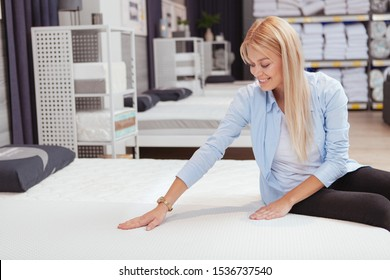 Cheerful beautiful woman trying orthopedic mattress at furnishings store, copy space. Bedroom, buying bed concept