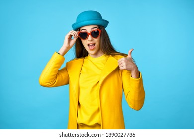 Cheerful beautiful woman in a yellow jacket blue isolated background lifestyle pattern make-up style hat on head