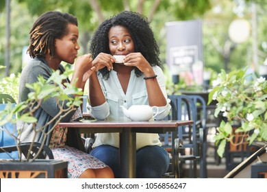 Cheerful beautiful women drinking tea and gossiping in outdoor cafe