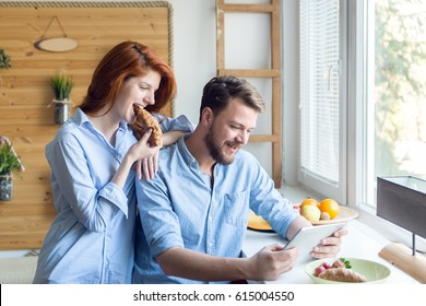 Cheerful beautiful young couple enjoying breakfast and using tablet