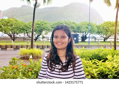 Cheerful beautiful young Indian woman feeling happy smiling to camera while wandering at Mauritius. Lifestyle backpack tourist travel holiday concept. Portrait looking at camera, soft warm filter