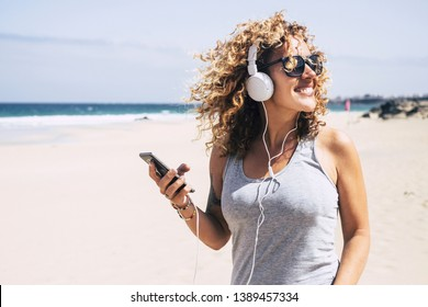 Cheerful beautiful young people blonde woman curly hair enjoying the summer holiday vacation at the beach listineg music from modern phone and headphones - sea and sand in background