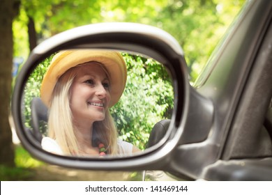 Cheerful beautiful young woman in the car, reflection in the mirror.