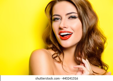 Cheerful beautiful young woman with charming smile over yellow background. Beauty, fashion. Cosmetics, make-up.