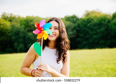 Cheerful and beautiful young woman holding a windmill toy in a green landscape