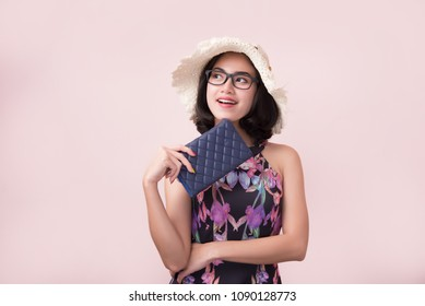 Cheerful Beautiful Young Woman in a Pretty mini dress with flowers holding wallet on pink background. Lifestyle and Summer Fashion. Shoping and Fashion. Fashion Spring Summer.