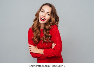Cheerful beautiful young woman in red sweater over gray background
