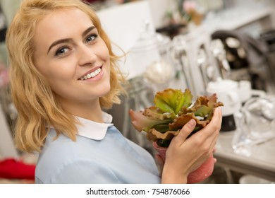 Cheerful beautiful young woman smiling to the camera holding potted plant while shopping at the homeware store copyspace cozy supermarket shop consumerism gardening leisure lifestyle florist emotions