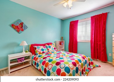 Cheerful bedroom interior in turquoise color with bright red curtains and colorful bedding