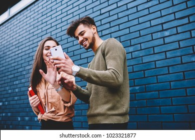 Cheerful best friends viewing funny photos in social networks via smartphone standing together on street, happy male and female hipsters watching funny online video content on mobile phone outdoors
