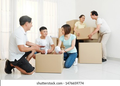 Cheerful big Vietnamese family packing belongings in cardboard boxes to move out