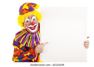 Cheerful birthday clown points at a black white sign.  Isolated.