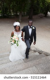 Cheerful black bride and groom holding hands on wedding ceremony