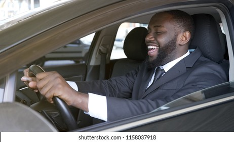Cheerful black businessman sitting in luxury automobile, test drive, transport